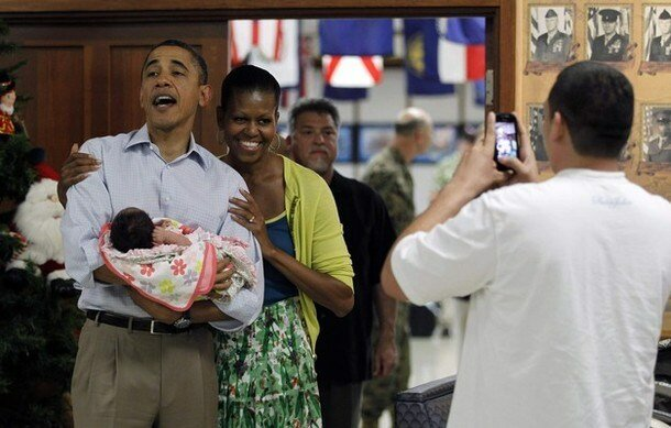 U.S. President Barack Obama and first lady Michelle Obama pose with a baby as they greet troops and their families at Kaneohe Bay Marine Corps base in Hawaii