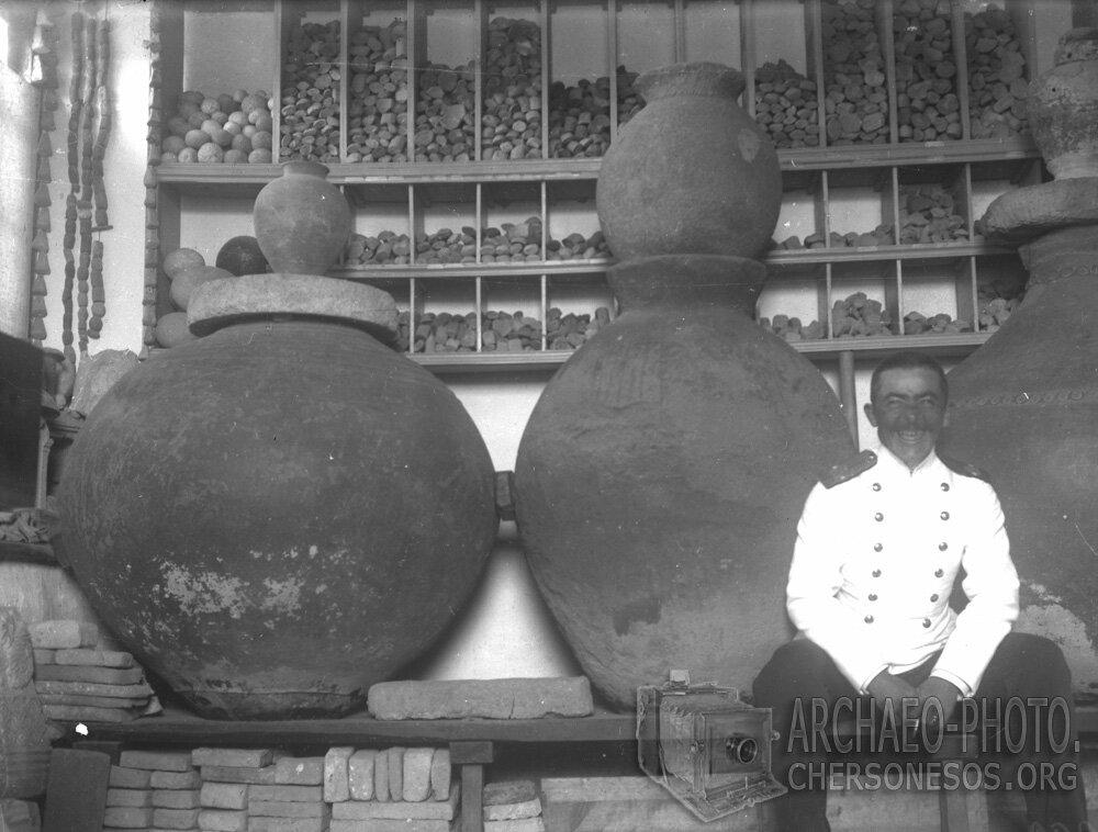 Неизвестный в помещении «Склада местных древностей» на фоне глиняных бочек – пифосо