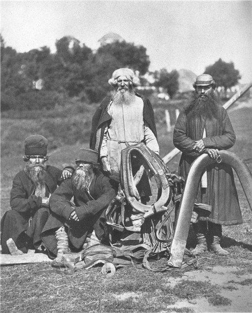 Мужчины с конской упряжью.Фотография начала XX в.Верхние одежды из домотканного сукна - армяки, поддевка из фабричной ткани (справа). Головные уборы - слева ямщицкая шапка, рядом - валяная шляпа с небольшими полями.
