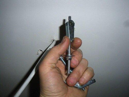 Фото 5. Шпилька-парашют продевается в отверстие в сложенном состоянии. С обратной стороны гипсокартоного листа пружина сама расправит лапки-фиксаторы.