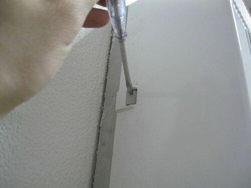 Фото 3. С целью доступа к электроустановочным изделиям щита мастер отжимает защёлку и снимает крышку пластикового шкафа.