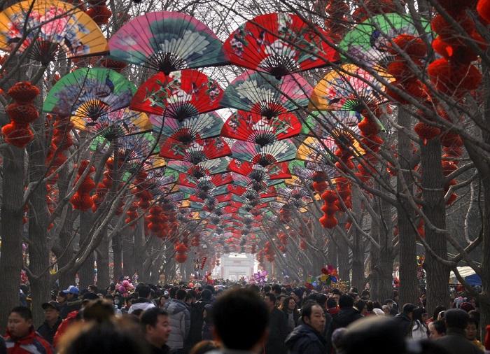 Толпы людей ходят среди деревьев, украшенных красными фонарями на храмовой ярмарке в честь празднова