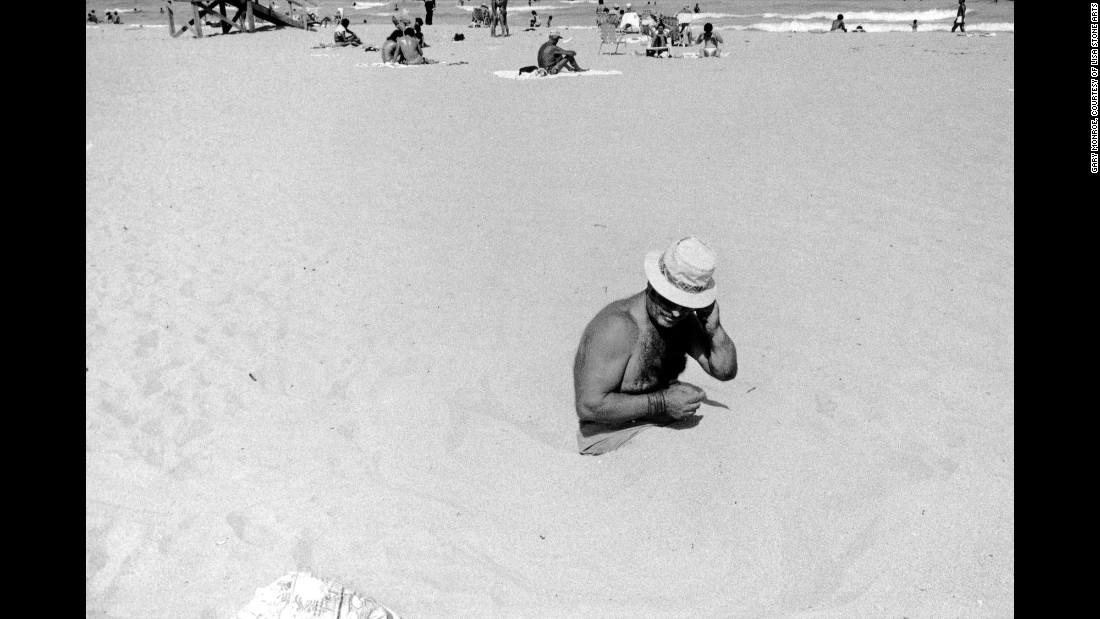 Мужчина сидит в песке на пляже парка Люммус, 1980. «Эти люди столкнулись когда-то с худшими проявлен