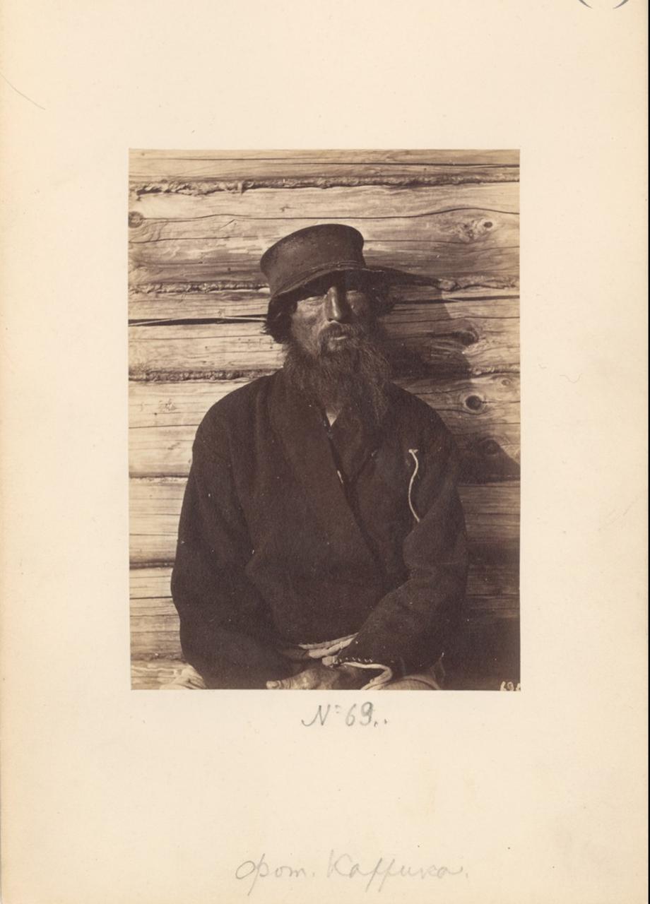Крестьянин на фоне избы. 1870-е