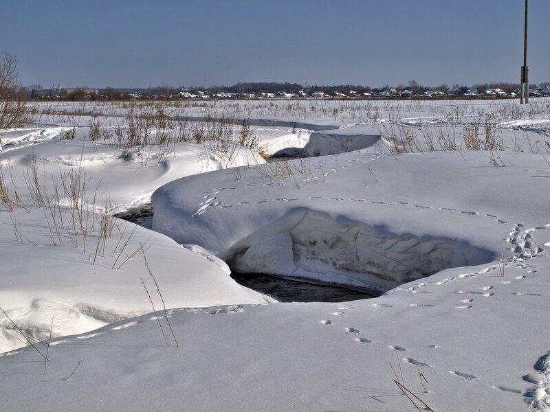 Петляющий среди снежных подушек ручей в Заречном