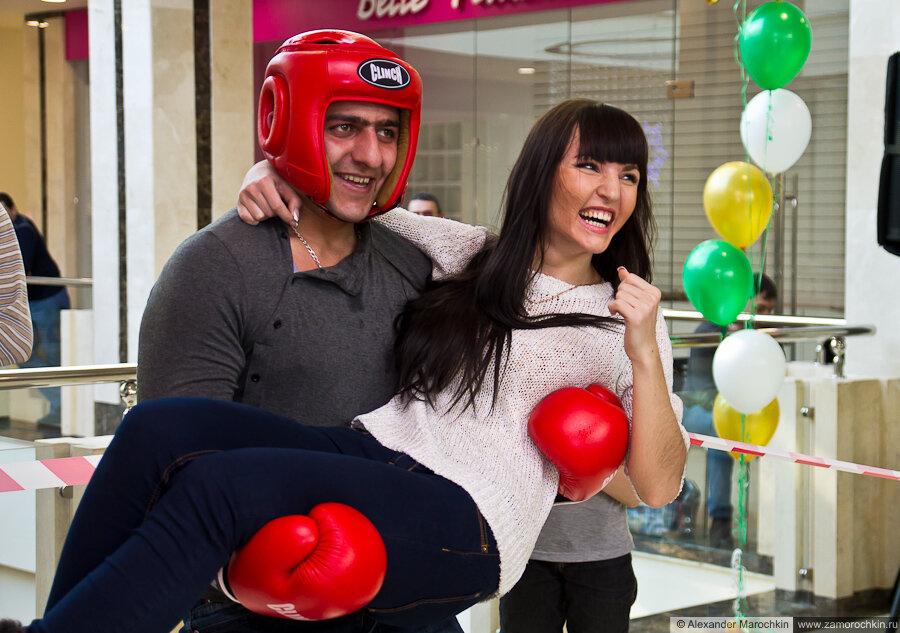 Приседания с девушкой на руках в боксёрской амуниции