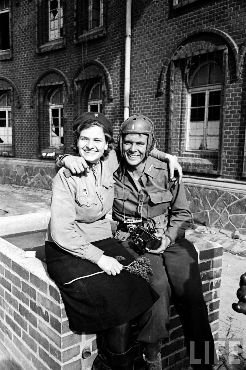 Русская солдатка и американский солдат сидят вместе после встречи союзников в районе города Торгау