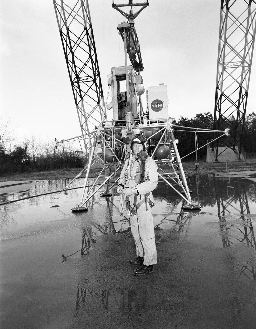 1969, 12 февраля.  Пилоты тренировались на модели лунного модуля, которая подвешивалась к высокой башне-крану на тросах, чтобы компенсировать 5/6 массы тренажёра. На снимке Нил Армстронг перед тренажёром лунного модуля, подвешенным к башне-крану