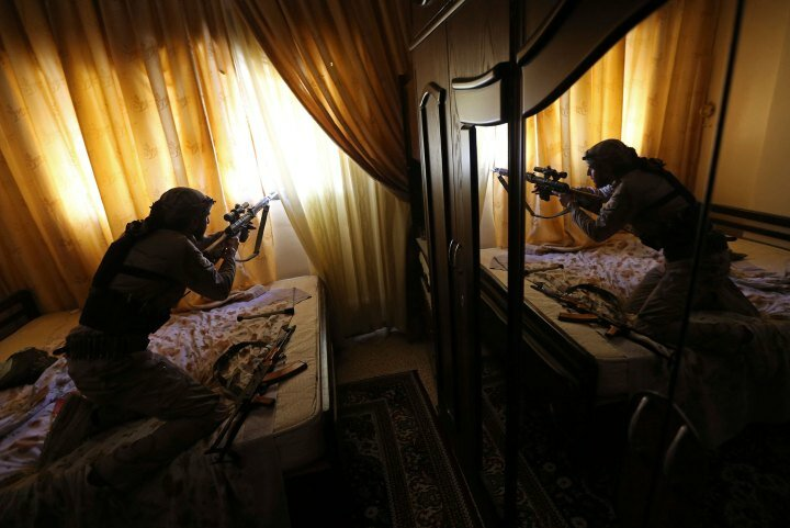 A fighter from the Sadik unit of Free Syrian Army's Tahrir al Sham brigade fires his Draganov sniper rifle from inside a house during heavy fighting in Mleha suburb of Damascus