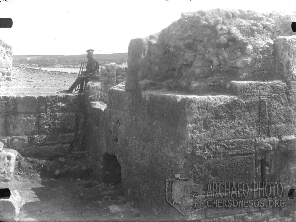 Рабочий с пилой, сидящий на античной башне у входа в «Цитадель»