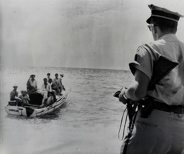 Awaiting U.S. Customs officials, a police officer holds off a boatload of Cuban defectors claiming to be starving farmers from the island