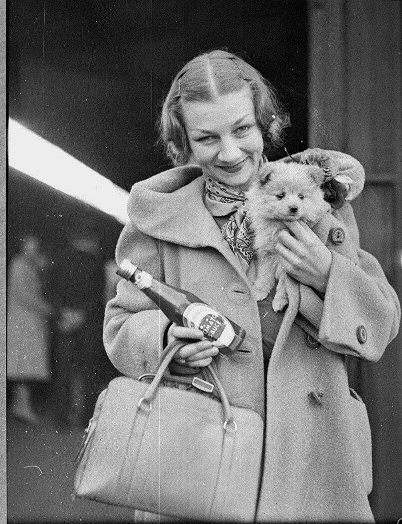Элен Кирсова с щенком и бутылкой с томатным соусом на бутылки по прибытии обратно в Сидней для возвращения сезоне, Центральном железнодорожном вокзале Сиднея, май 1937