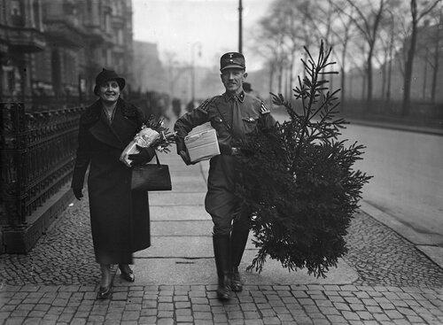 SA-Mann in Begleitung einer Frau mit Weihnachtsbaum und Geschenkpaketen in der Vorweihnachtszeit auf der StraЯe