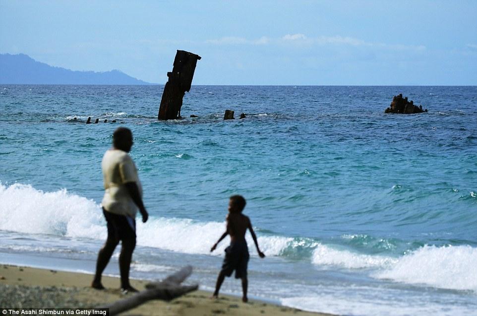 Местные жители играют и гуляют возле обломков транспортного корабля императорского флота Японии «Кин