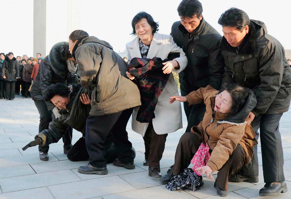 26. Жители Пхеньяна не в силах стоять на ногах от боли и печали от утраты лидера страны. (Reuters/Ky
