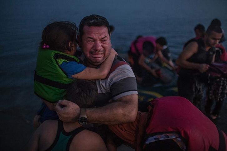 Лаит Маджид из Ирака расплакался, держа на руках дочь и сына, когда они благополучно добрались до Ко