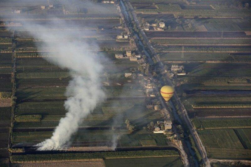 Дым поднимается от горящих костров, в которых фермеры сжигают солому после уборки урожая на западном берегу реки Нил в Луксоре, Египет.