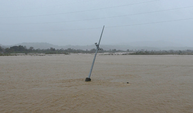 A utility pole is partially submerged in a river after Typhoon Haima struck San Nicolas, Ilocos Nort