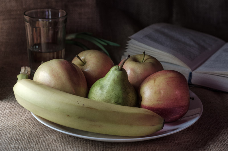стакан, тарелка с фруктами, книга и льняная ткань