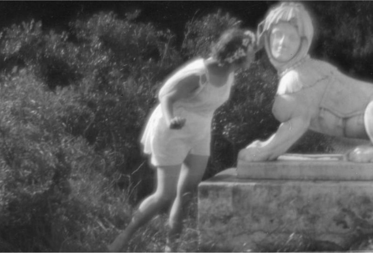 Девушка в тунике у скульптуры сфинкса