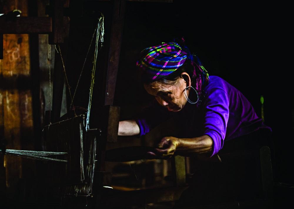 Женщина племени хмонг ткет традиционную одежду.