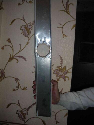 Фото 2. Демонтированная алюминиевая рейка левой части подвесного потолка с безобразно выполненным отверстием под точечный светильник. Вид с внутренней стороны рейки.
