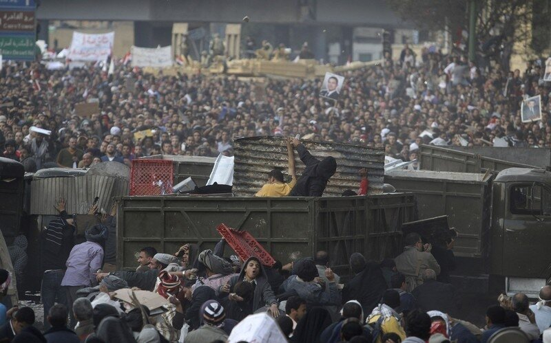 Anti-government supporters throw stones over a barricade at pro-Mubarak supporters during clashes at Tahrir Square in Cairo