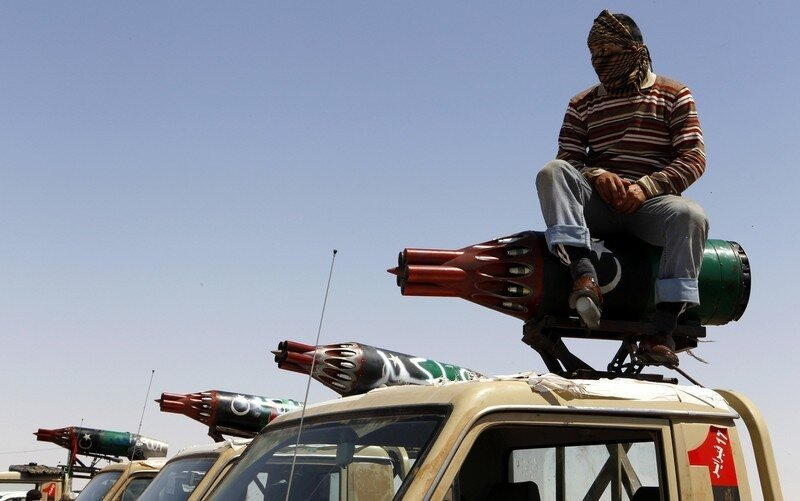 A rebel fighter sits atop pick-up trucks mounted with rocket launchers taken off helicopter gunships, at the frontline along the western entrance of Ajdabiyah
