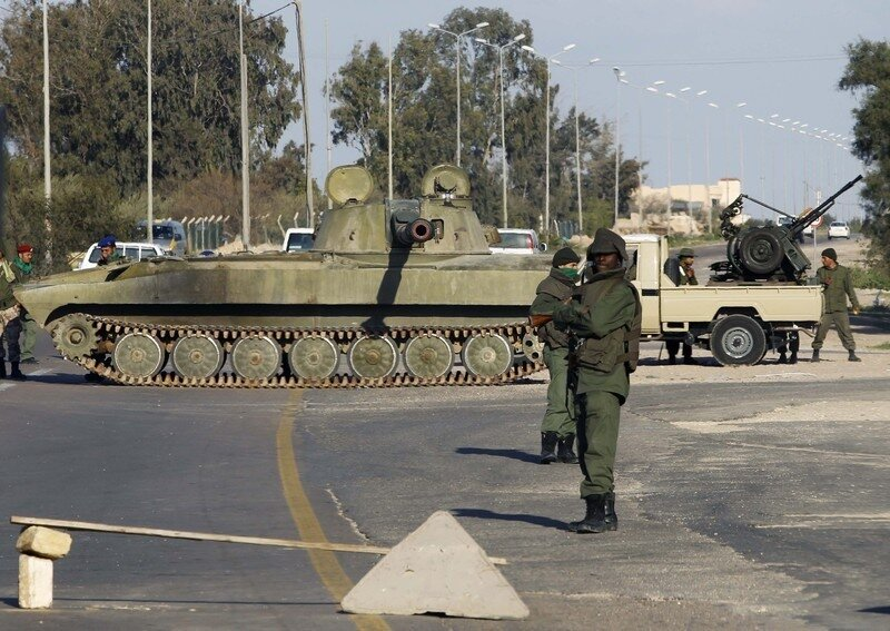 Libyan troops loyal to leader Muammar Gaddafi guard a checkpoint between the capital and the city of Zawiyah
