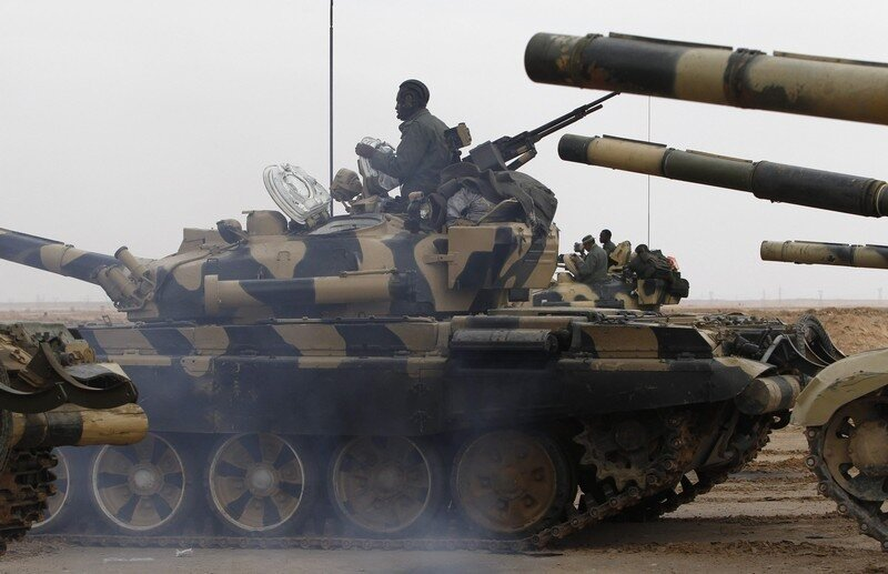 Libyan government soldiers drive their tank at the west gate of town Ajdabiyah