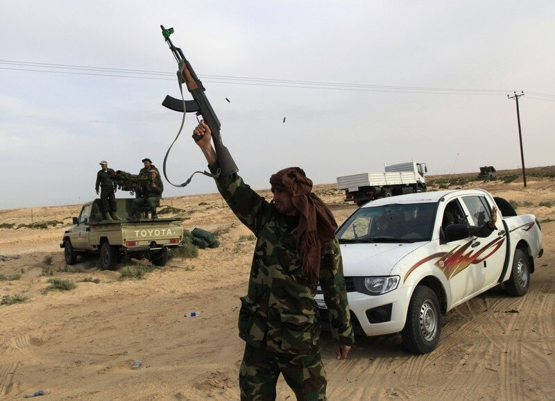 A Libyan government soldier fires in the air at the west gate of  town Ajdabiyah