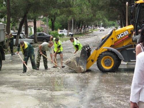 Рабочие чистят улицы после наводнения