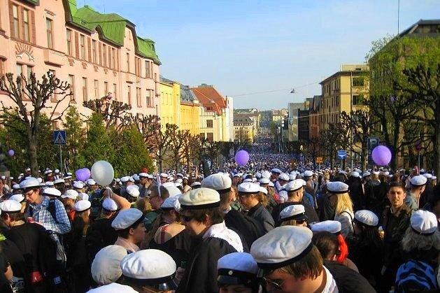 Празднующие первомай интеллигенты в белых фуражках заполняют финские города