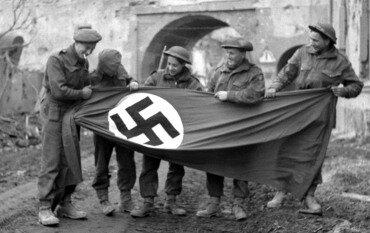 Канадские солдаты с захваченным вражеским флагом.