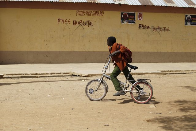 A boy rides a bicycle past political posters and graffiti in Zaria, Kaduna state, Nigeria, February