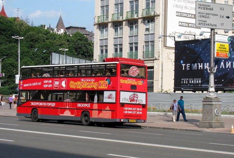 Красный экскурсионный автобус на улицах Киева