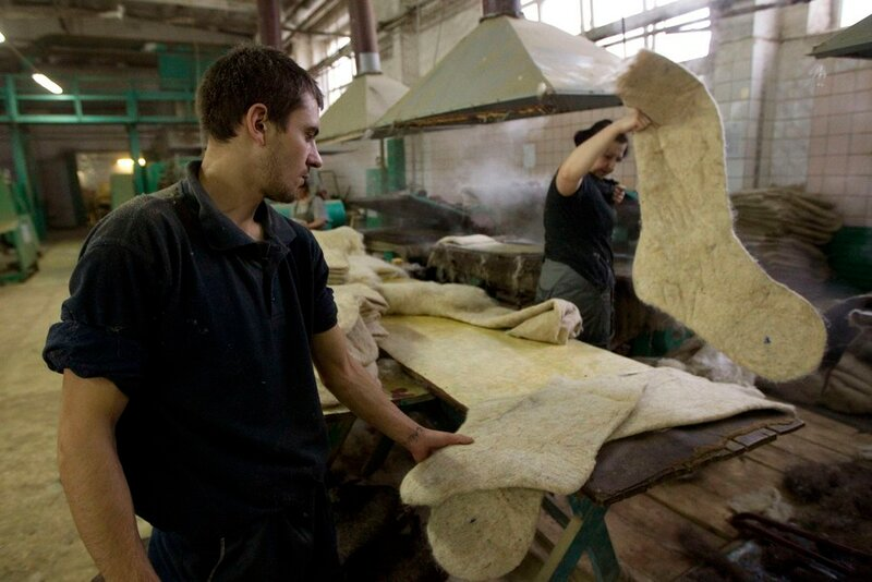 Workers process semi-finished valenki, traditional footwear made of raw wool, at a factory in village of Smilovichi