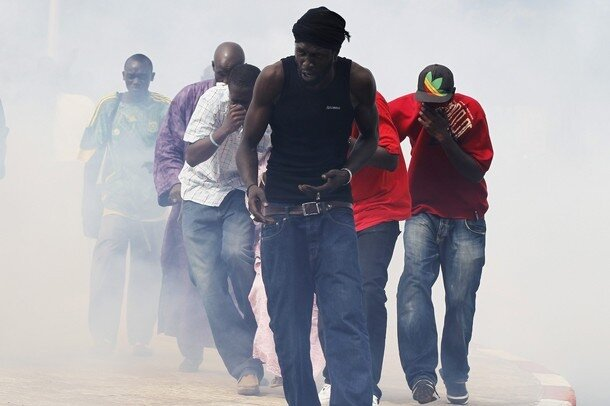 Protestors cover their mouths as they run through a cloud of tear gas during a demonstration in Senegal's capital Dakar