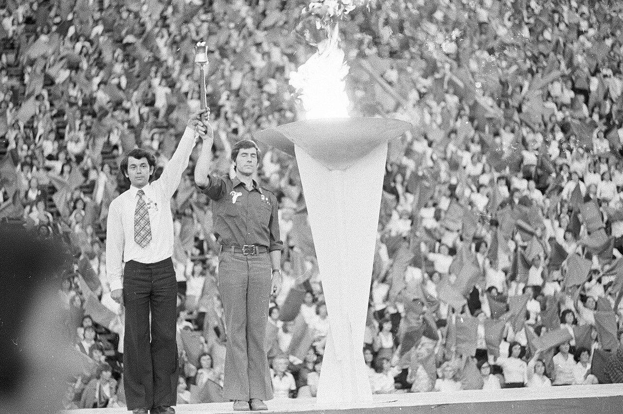 Представители Советского Союза и ГДР вместе держат факел после того, как они зажгли огонь в чаше Фестиваля