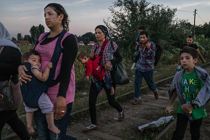 Ружин Шейхо из Сирии (слева) несет свою дочь Видад, а ее сын Наби (справа) шагает вместе с другими б