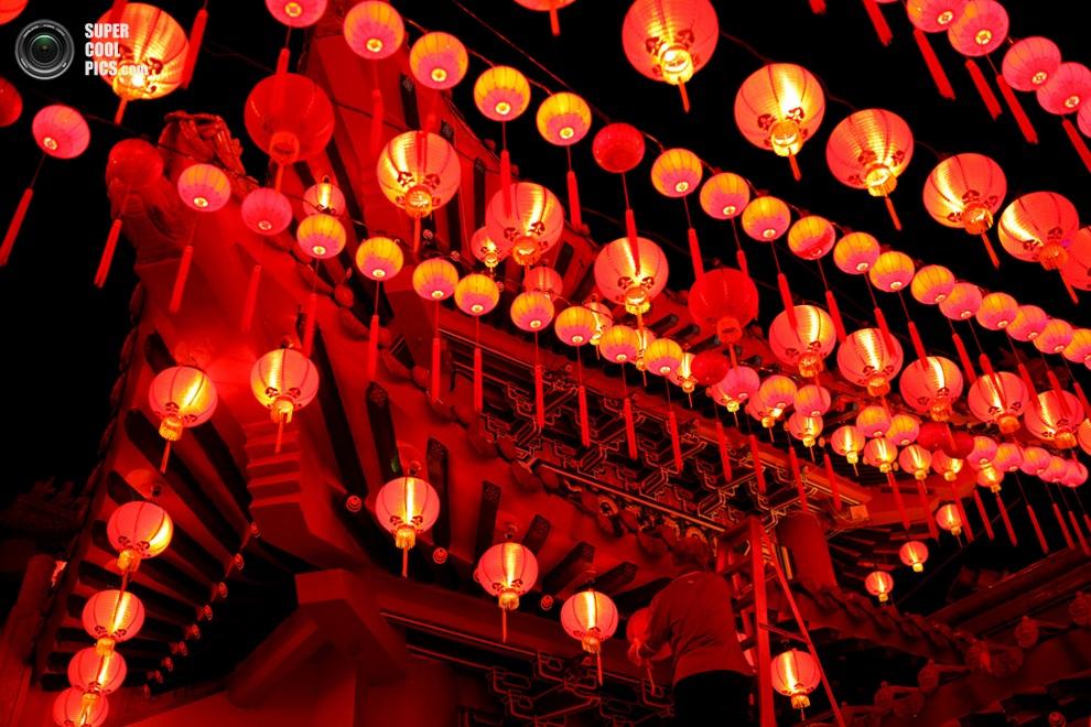 Работник китайского храма Тхеан-Хоу в Куала-Лумпуре, Малайзия,зажигает фонарики в преддверии Пр