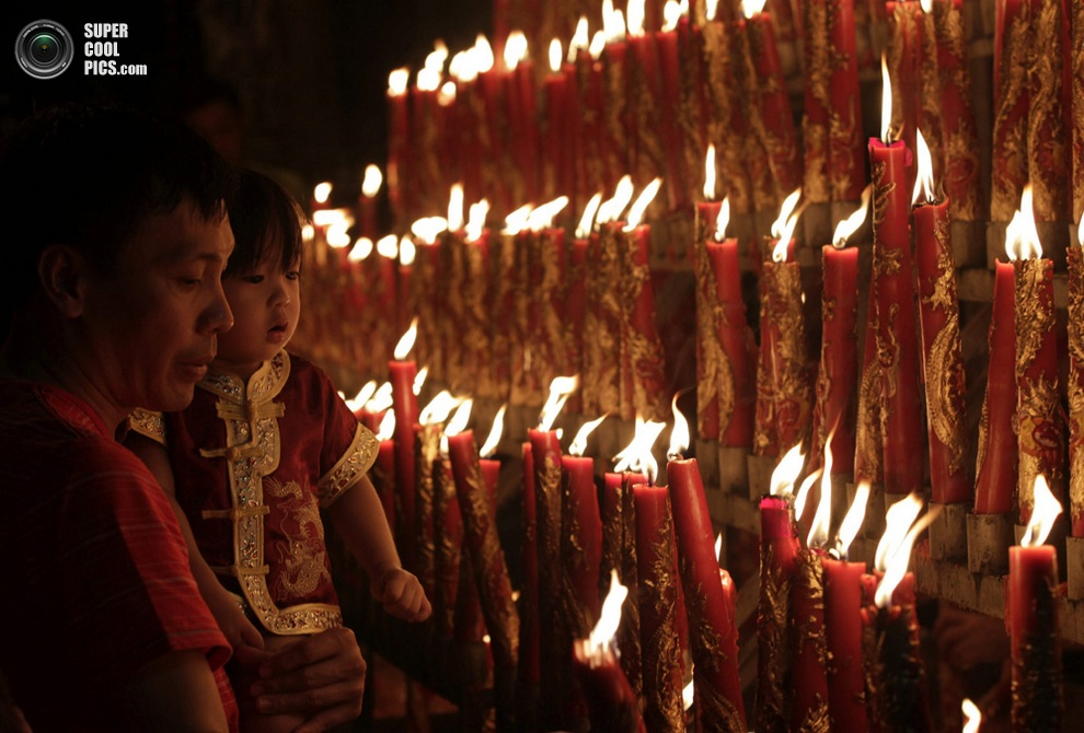 Отец со своим чадом зажигает свечи в буддийском храме, Манила, Филиппины.(EFE/EPA/DENNIS M. SAB