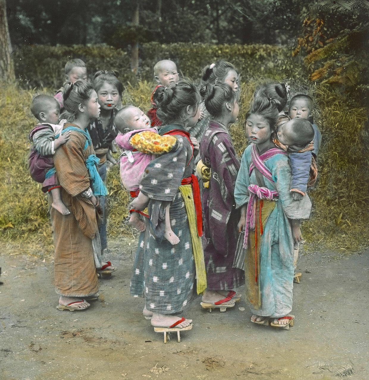 Девочки и женщины в кимоно с грудными детьми на спине