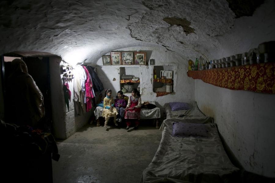 22. Дети сидят в пещере, которая служит жилищем для их семьи, в городе Хассан Абдал в Пакистане, 4 ф