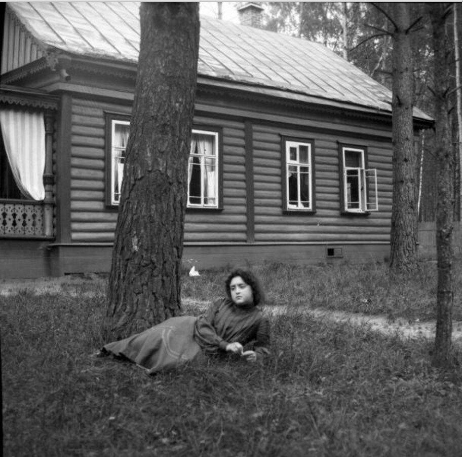 1904. Вешняки. Маня лежит около дерева в саду. Позади дача