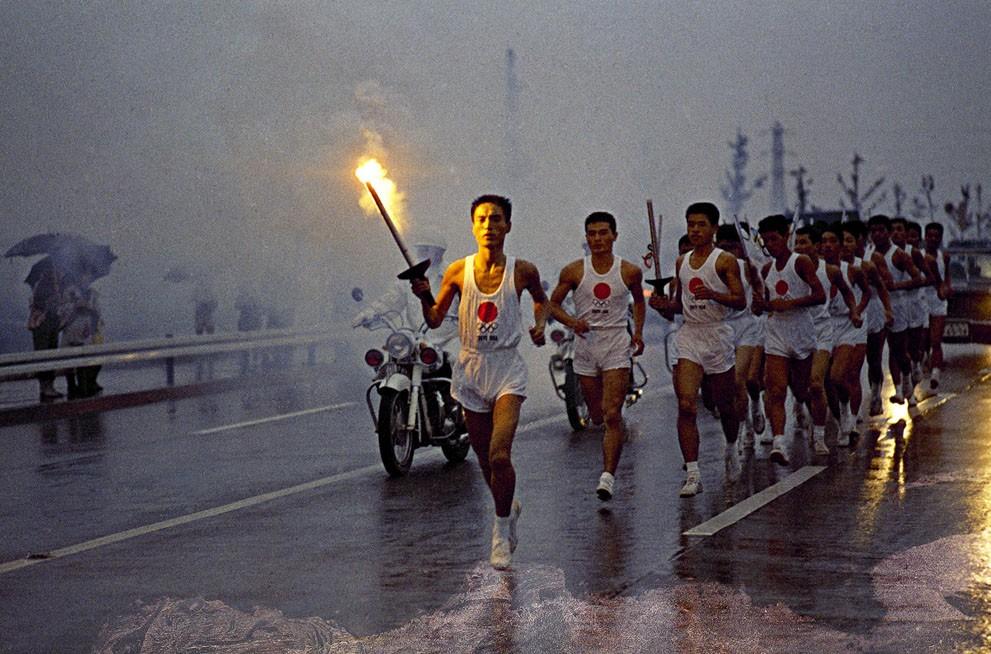 Факелоносцы направляются к олимпийскому стадиону в рамках эстафеты олимпийского огня в Токио, Япония, октябрь 1964 года.jpg