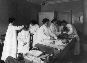 Воспитанницы института одевают детей грудного возраста.