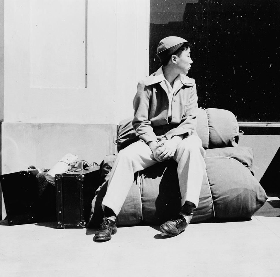Мальчик сидит на своих пожитках и ждет переселения из Сан-Франциско.