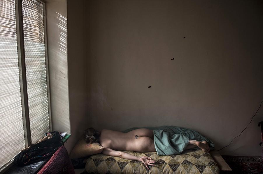 2. Обнаженная женщина на кровати в своем доме. Она вынуждена работать проституткой, чтобы прокормить