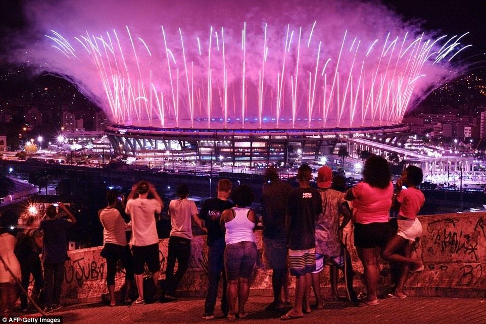 Люди наблюдают за фейерверками из фавелы Мангейра, с которой открывается отличный вид на стадион Мар